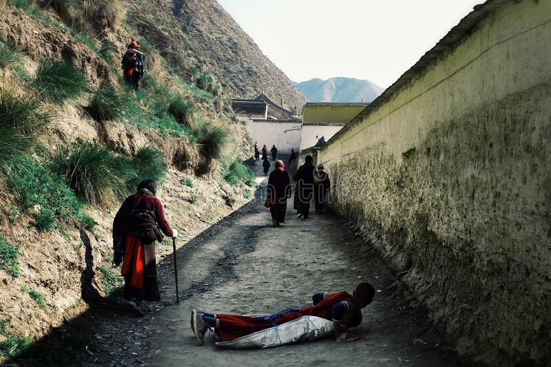 people walking around the tibetan buddhist monastery as a part of a pilgrimage circle in traditional dress while a young man layin stock image