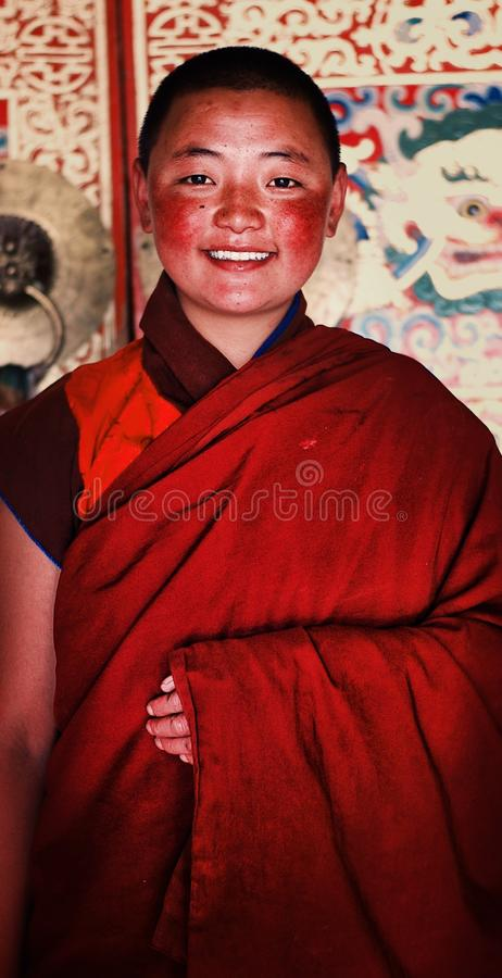 young tibetan buddhist nun in front of a highly decorated wall of her monastery royalty free stock photos