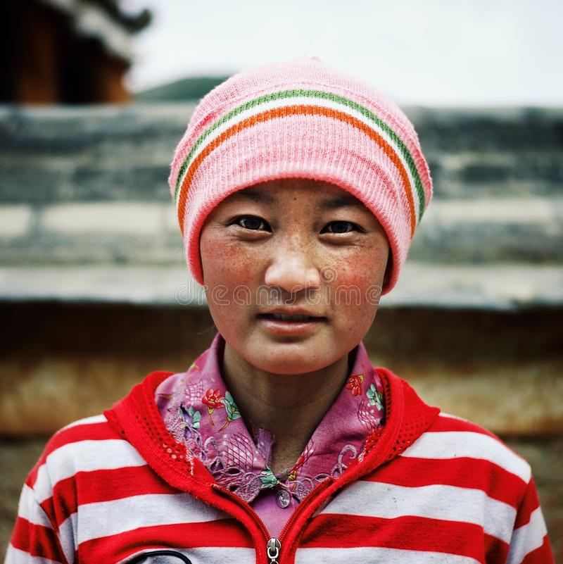 young tibetan buddhist pilgrim girl in front of the monastery wall stock photo