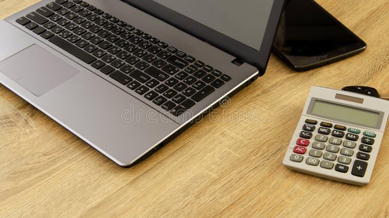 Labtop kalkulatora i komputeru biurowe dostawy na drewnie zgłaszają des obraz royalty free