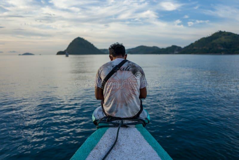 Labuan Bajo, Indonésia - 1º de abril de 2018: Homem local no barco no porto de Labuan Bajo imagens de stock