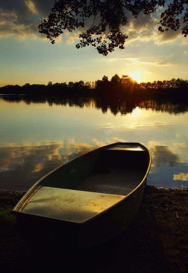 Lac au coucher du soleil avec un bateau images stock