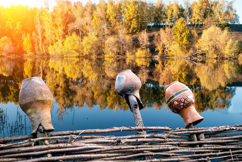 Lac avec des arbres et barrière en osier avec des cruches images stock