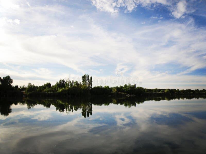 Lac avec le ciel et les nuages se reflétant en rivière tranquille images libres de droits