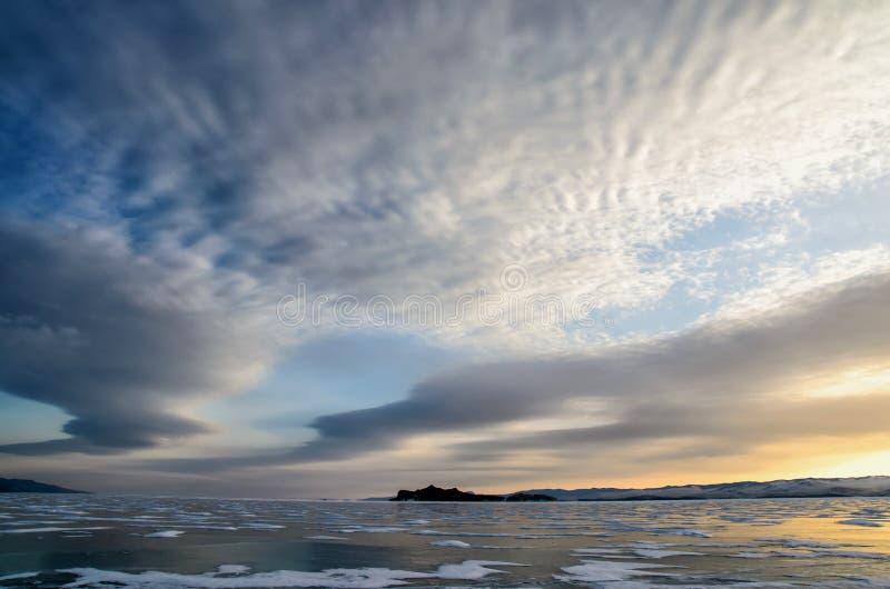 Lac Baikal figé Les beaux nuages stratus au-dessus de la glace apprêtent un jour givré photographie stock