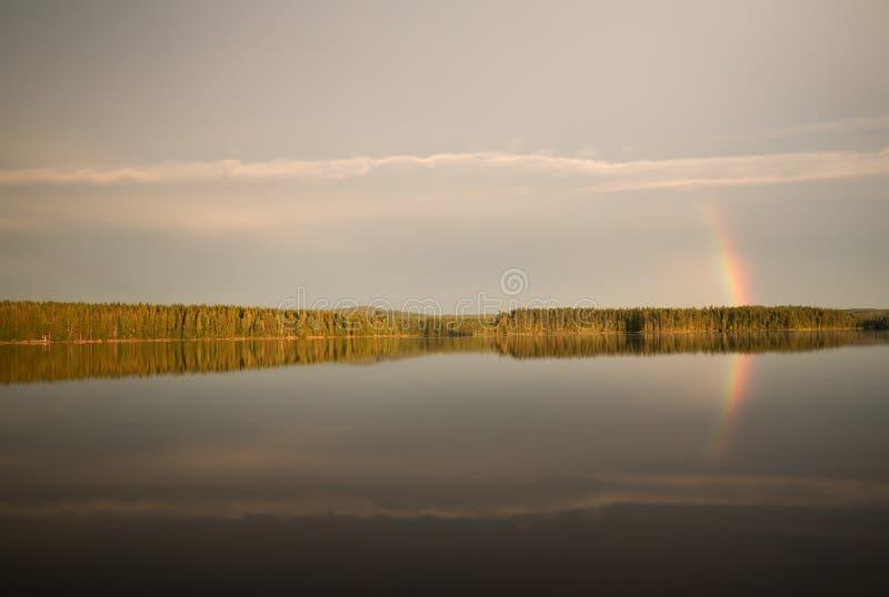 Lac calme en Suède avec l'arc-en-ciel réfléchissant sur la surface image stock