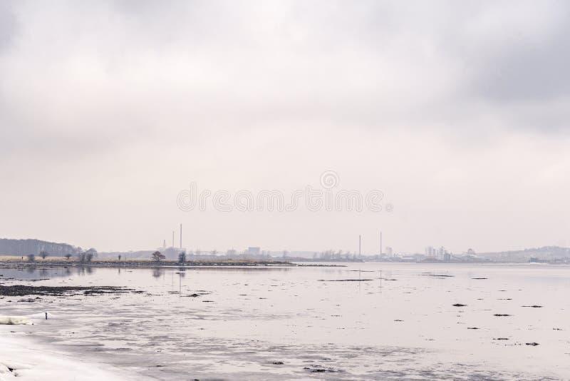 Lac congelé par une ville avec les bâtiments industriels image stock