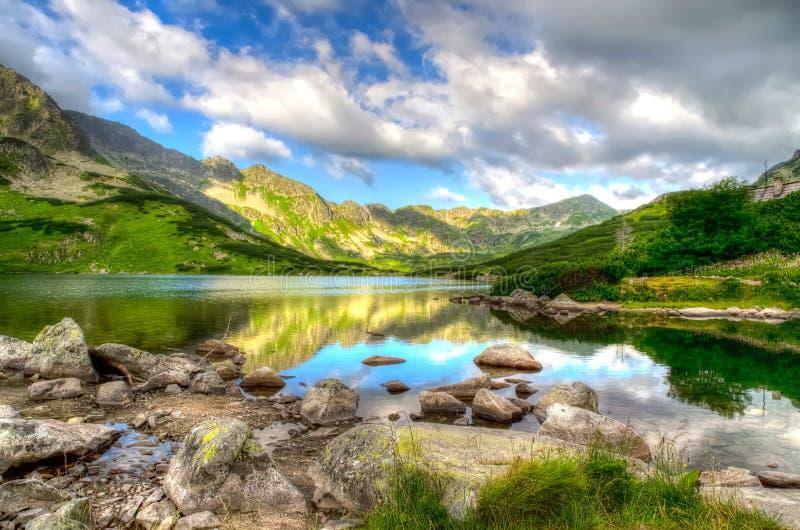 Lac dans le mountainsin dans les couleurs de début de la matinée images libres de droits