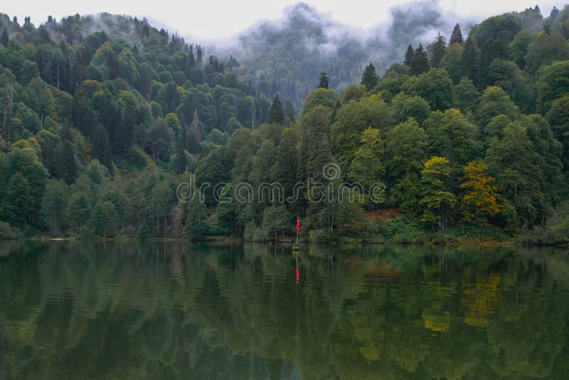 lac et forêt brumeuse en montagnes dans un jour pluvieux photos stock