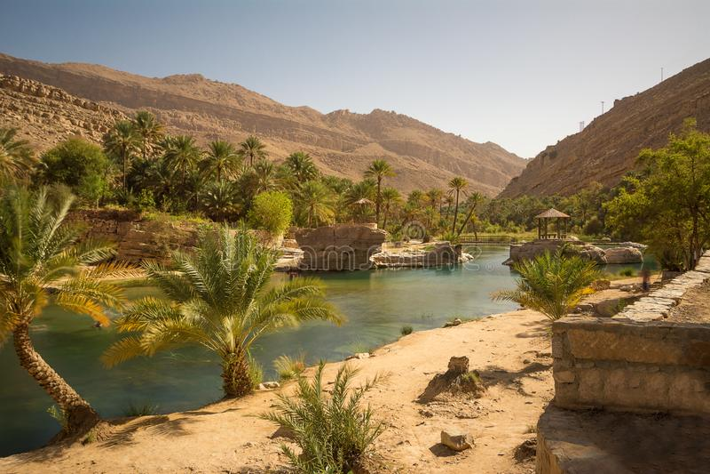 Lac et oasis avec des palmiers Wadi Bani Khalid dans le désert omanais image stock