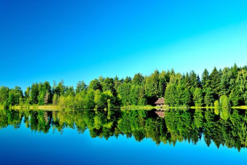 Lac forest avec un sauna sur le rivage images libres de droits