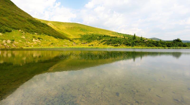 Lac mountain avec les collines vertes photo libre de droits
