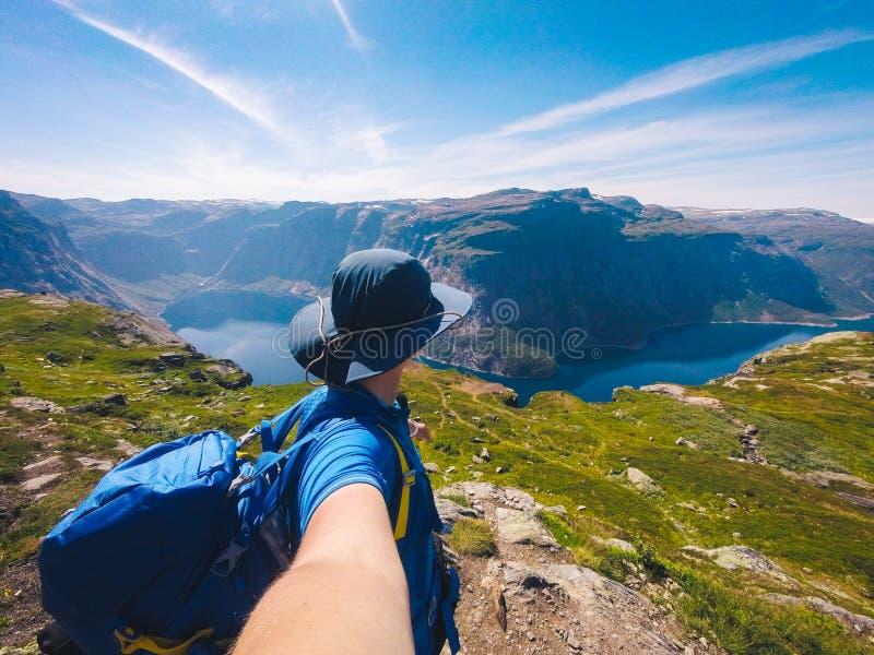 Lac Ringedalsvatnet pr?s de Trolltunga Lac bleu en Norv?ge La touriste de femme dans le chapeau et le sac à dos recule et tient l photographie stock libre de droits