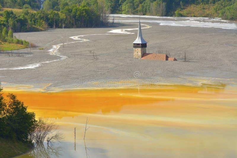 Lac rouge pollué avec des arbres morts et une église inondée image stock