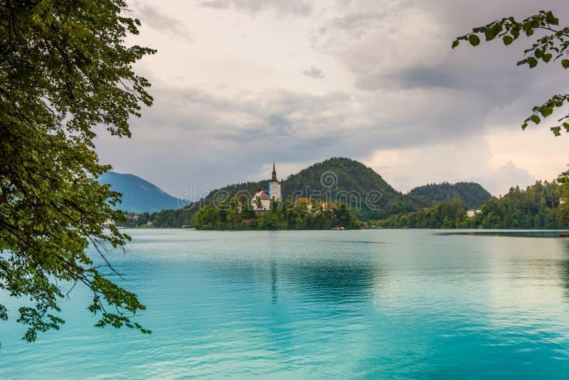 Lac saigné avec l'île et l'église L'eau bleue et nuages de tempête images stock