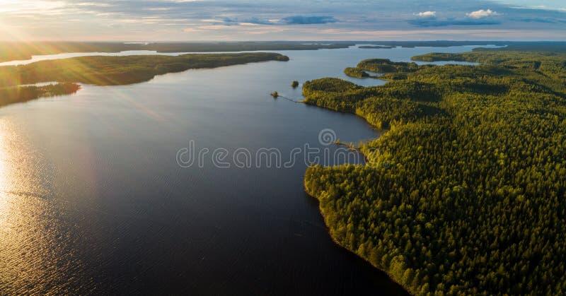 Lac Suoyarvi au coucher du soleil entour? par des for?ts de la Car?lie images libres de droits