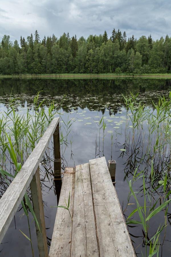 Lac tranquille et calme et un pilier en bois en Finlande images stock