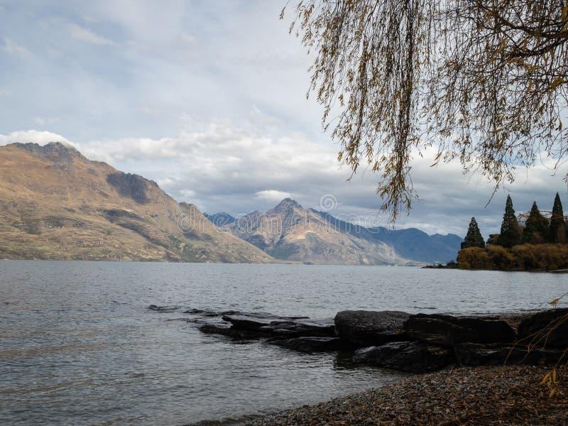 Lac Wakatipu, Queenstown, ciel nuageux à travers la montagne et un saule photo libre de droits