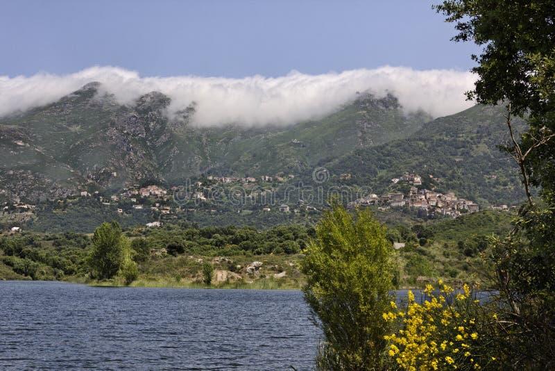 Laca de Padula (lago Padula), no fundo a aldeia da montanha Oletta na região de Nebbio, Córsega do norte fotos de stock royalty free