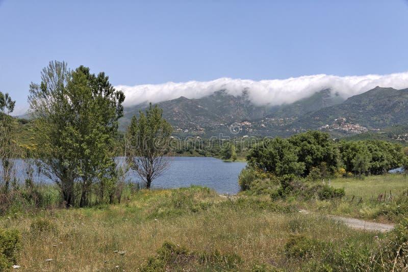 Laca de Padula (lago Padula), no fundo a aldeia da montanha Oletta na região de Nebbio, Córsega do norte, França fotografia de stock