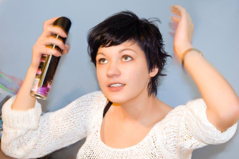 Lacca di spruzzatura dei capelli della ragazza sui suoi capelli fotografia stock libera da diritti