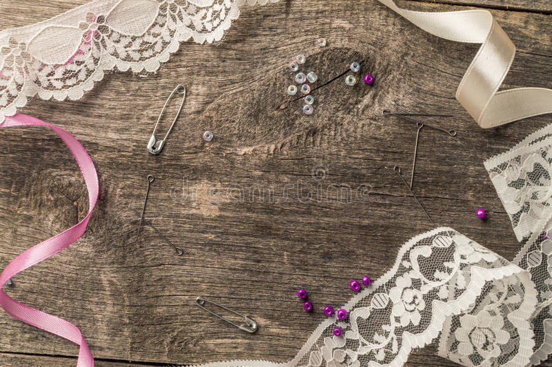 Lace, beads, sewing supplies on wooden background. Top view. Flat lay composition royalty free stock image