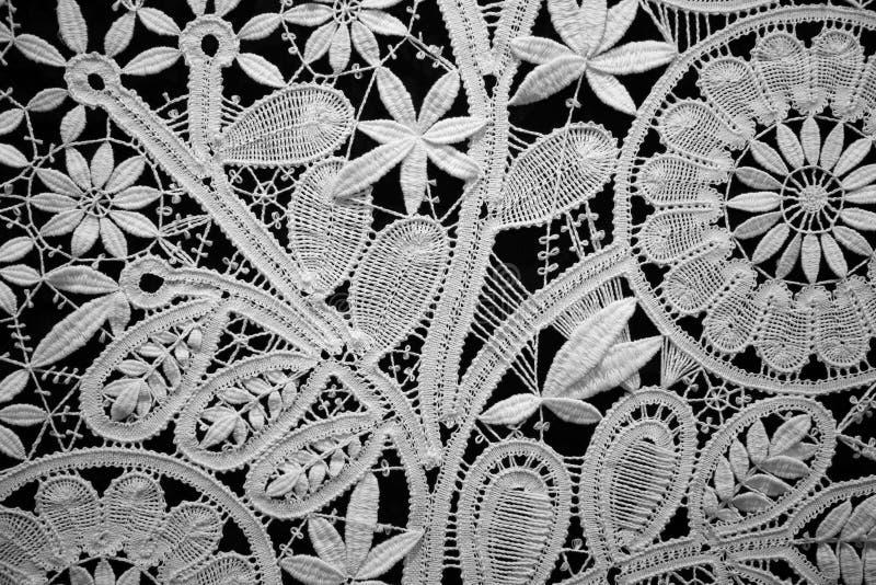 Lace doily on black background, close up stock photo