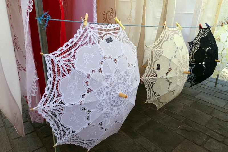 Lace Parasols Handmade in Malta. Delicate lace parasols are for sale at the open-air Marsaxlokk Sunday market. The beautiful umbrellas offer shade from the hot stock photography