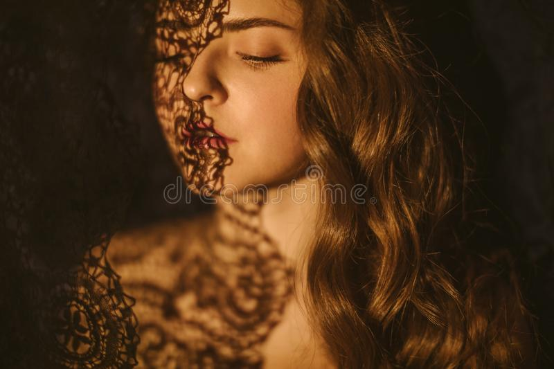 Lace and shadows. Sensual sexy portrait of a young woman. Beautiful long hair. royalty free stock image