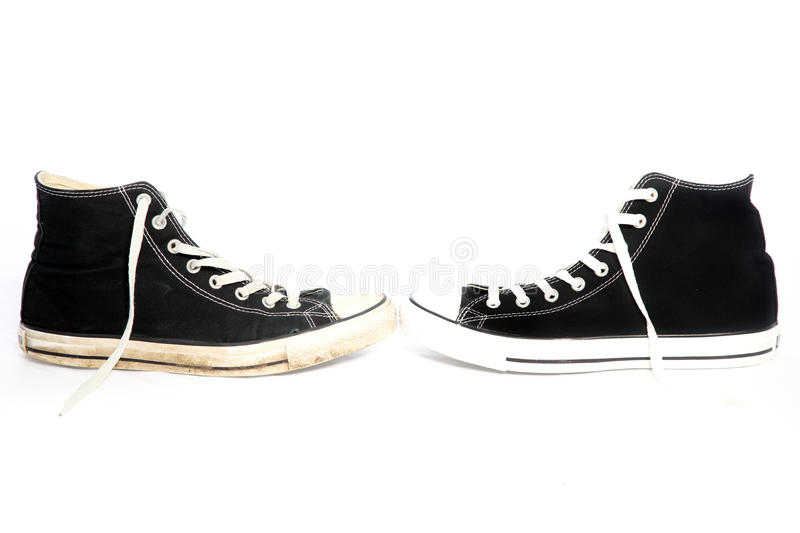 Laced sneakers on white. Pair of laced sneakers on a white background for casual wear arranged with their toes facing each other stock photos
