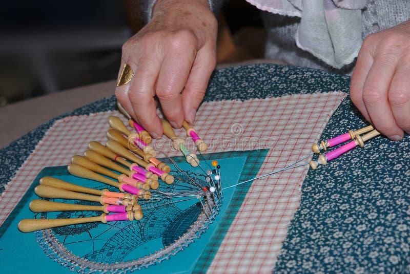 Lacemakers händer spolen snör åt arbete royaltyfria foton