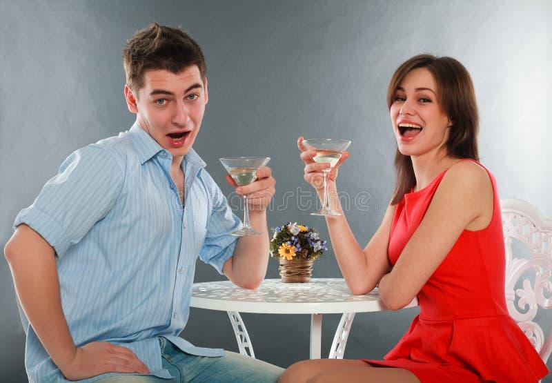 Lach en dronken paar met glazen champagne bij lijst stock afbeeldingen