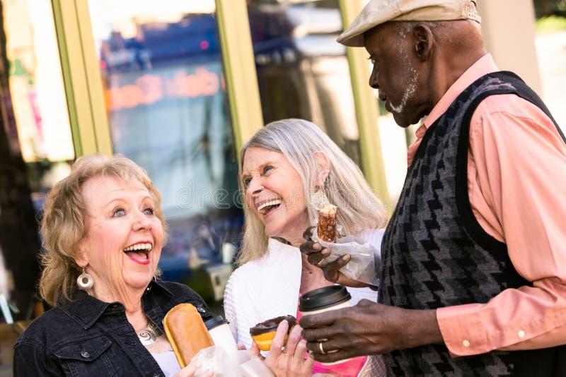 Lachen drei Senior-im Stadtzentrum gelegenes Essensdonutsand lizenzfreies stockfoto