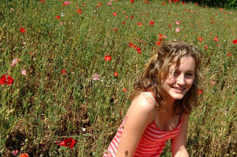Lachen jugendlich auf dem Blumengebiet stockbild