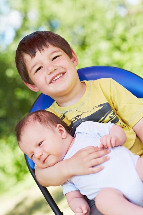 Lachen Junge hält Baby stockbild
