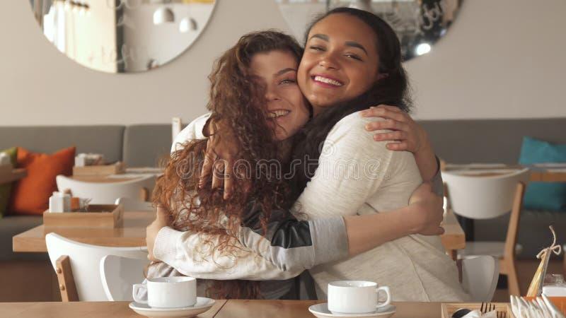 Lachen mit zwei Mädchen über das Café lizenzfreie stockbilder