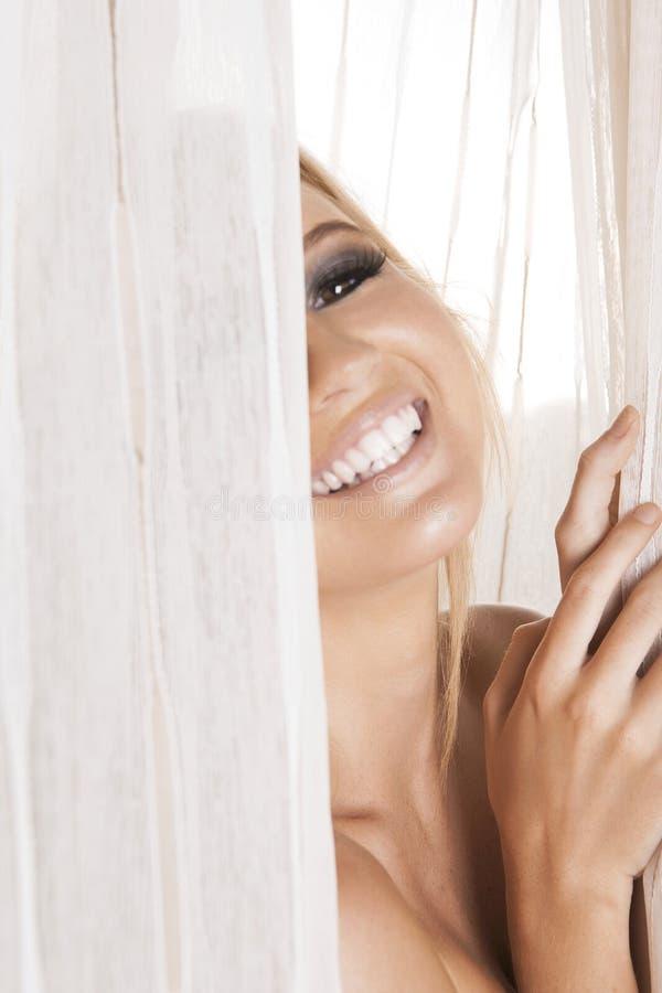 Lachend blonde achter de gordijnen stock afbeeldingen