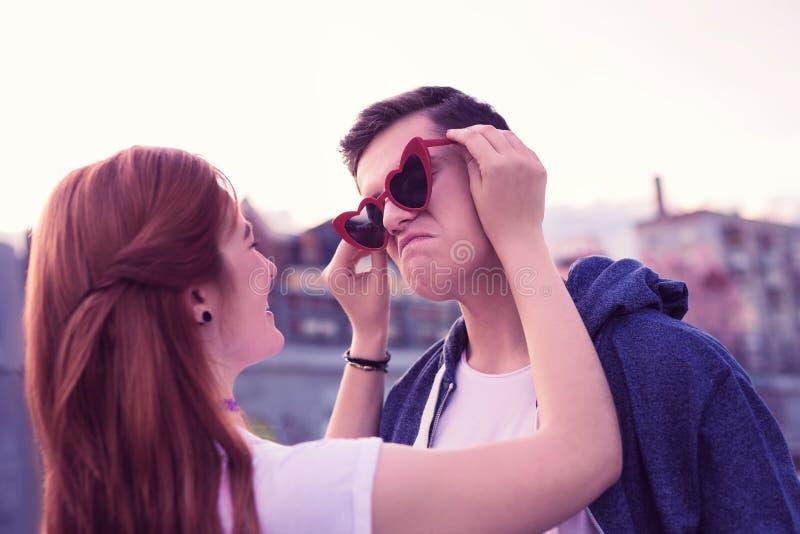 Lachend gembermeisje die funky rode zonnebril vastmaken aan het gezicht van haar vriend stock afbeelding