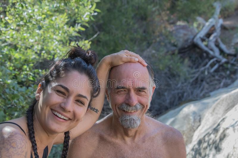 Lachend, glimlachend, hogere rijpe vader met Spaanse dochter buiten in aard die pret hebben samen stock foto