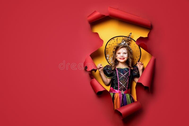 Lachend grappig kindmeisje in een heksenkostuum in Halloween royalty-vrije stock foto