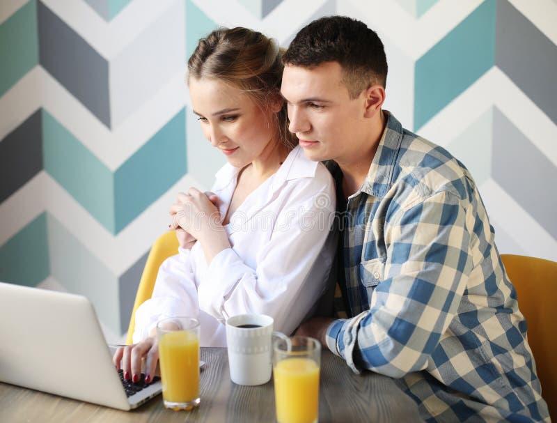 Lachend houdend van paar die ontbijt hebben terwijl het zitten bij de lijst in een keuken thuis en het bekijken laptop computer stock fotografie