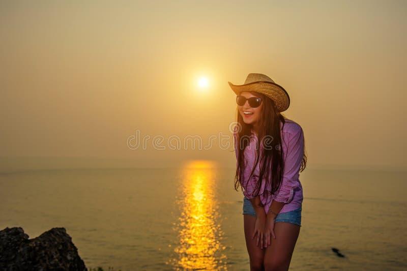 Lachend jong meisje in de zomerhoed en zonnebril die mooie zonsondergang overzien Rust op het overzees, reis, het gelukkige leven royalty-vrije stock afbeeldingen