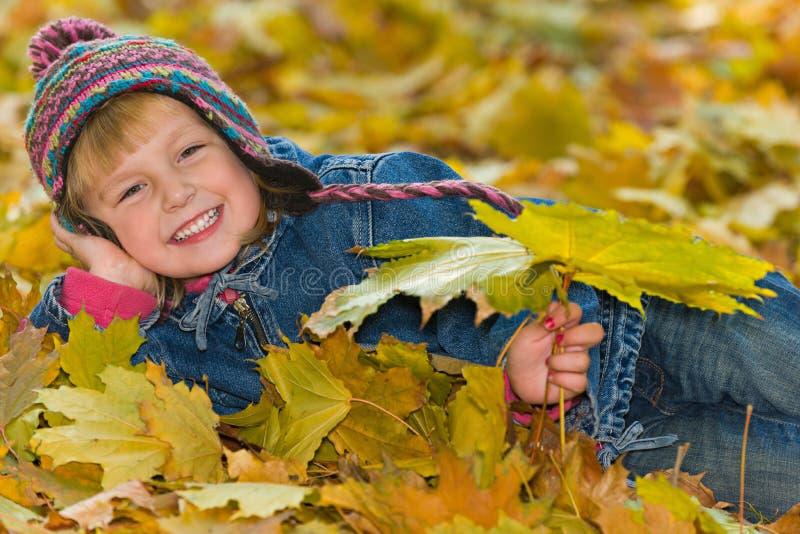 Lachend jong meisje op de gele bladeren royalty-vrije stock afbeelding