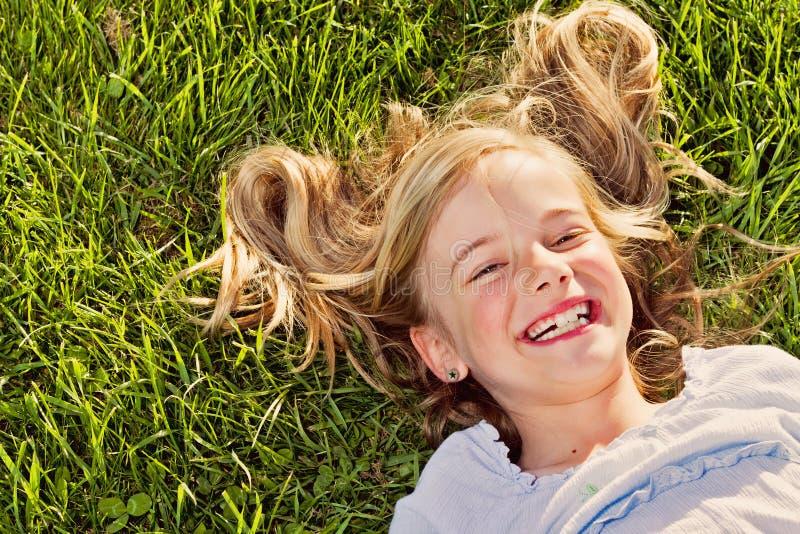 Lachend meisje dat in gras ligt stock foto