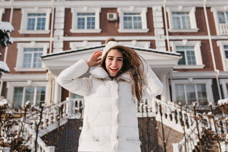 Lachend meisje die met donker haar van warme de winter dag en het maken van grappige gezichten genieten Openluchtfoto van onbezor stock afbeelding