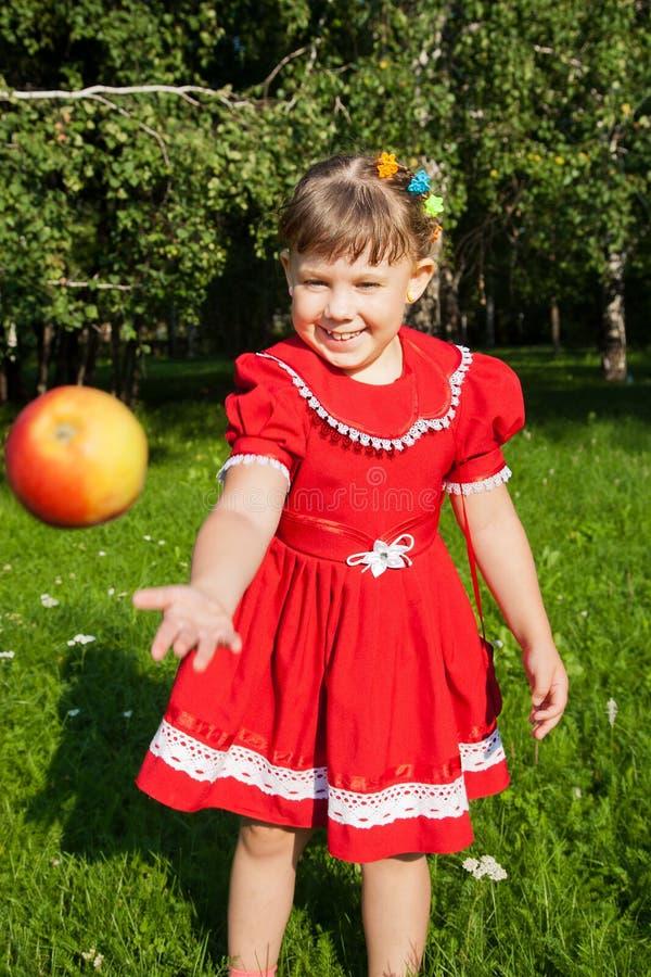 Lachend meisje die werpen op redapples royalty-vrije stock afbeelding
