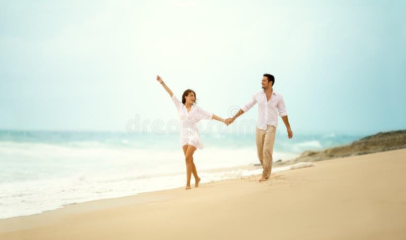 Lachend paar in de hand van de liefdeholding op strand stock foto's