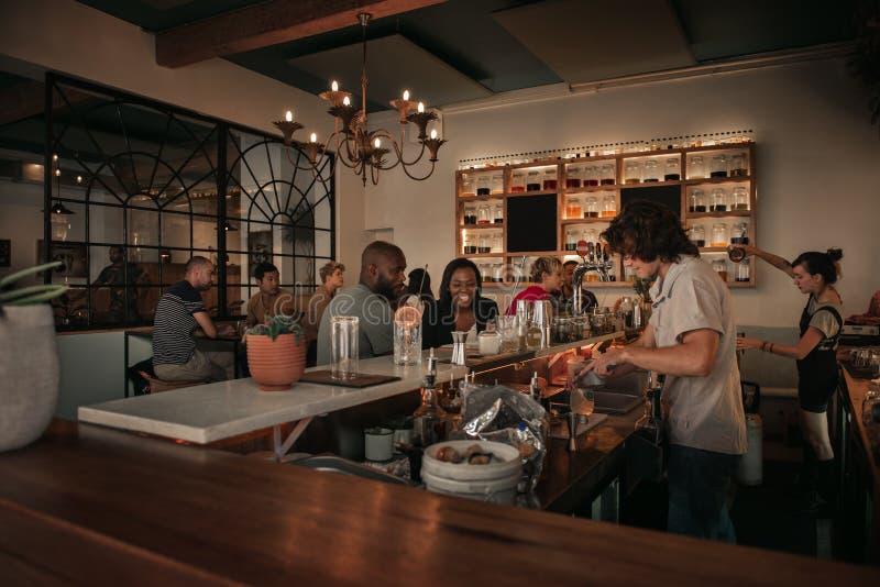 Lachend paar die met een barman in een bar spreken royalty-vrije stock foto
