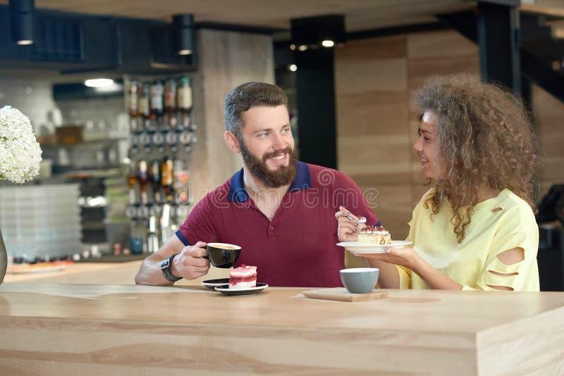 Lachend paar die van jonge studenten die koffie drinken, cakes in koffie eten stock foto
