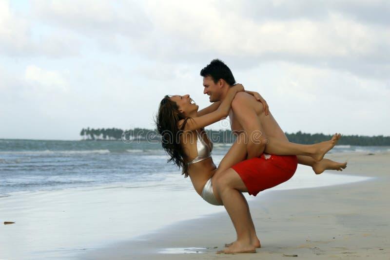 Lachend paar op het strand stock foto